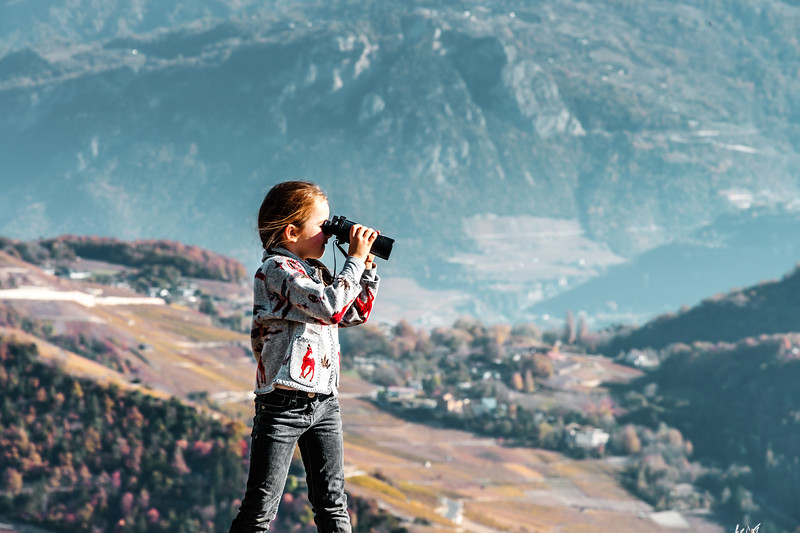 Cute little girl investigating Alps mountains using binocular. Touristic concept.