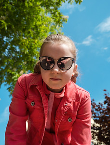 Little schoolgirl posing in beautiful sunglasses and a red suit in the sun in a park