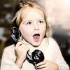 Little girl speaking vintage telephon