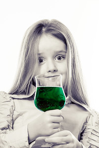 Little girl with glass of vivid green liquid, maybe poison