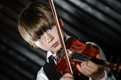 Attractive boy playing violin, studio shooting