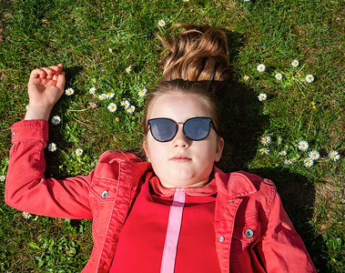 A schoolgirl with long hair in red clothes lies on the green grass among spring flowers. Portrait from above.