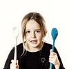 Preschooler girl playing with spoons for salad