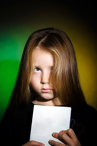 Cute little girl with long hair showing book