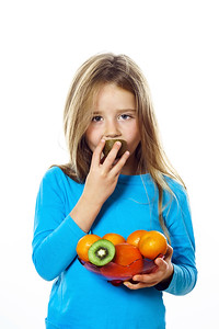 Cute little girl with plate of fruits: kiwi, date plum, mandarins, etc.