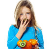 Cute little girl with plate of fruits: kiwi, date plum, mandarins, etc.