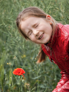 Girl schoolgirl near a red poppy in the field