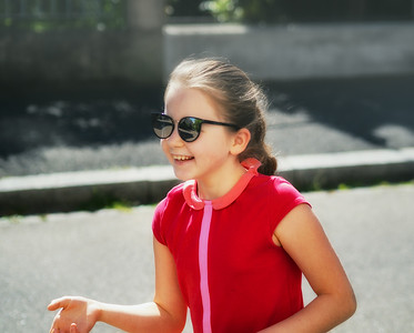Emotional photos of a schoolgirl girl who runs along the street in the bright sun.