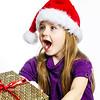Cute little preschooler girl in red santa hat with gift box