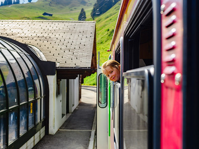 Little girl looking through the window of alpine train