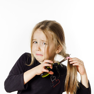 Cute little girl with scissors. Self hairdresser