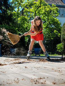 A schoolgirl poses with a broom in the yard, while rollerblading. Housekeeper. Sweeping in the garden.