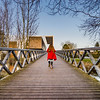 Little girl skating on the long wooden bridge over the river