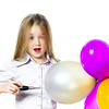 Funny little girl blowing up colorful baloons