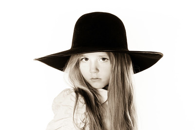LIttle girl posing like a model in mother's hat