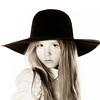 LIttle girl posing like a model in mother's hat