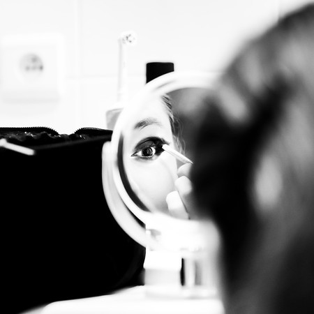 A beautiful young girl paints her eyes in front of a small mirror. Normal daily life.