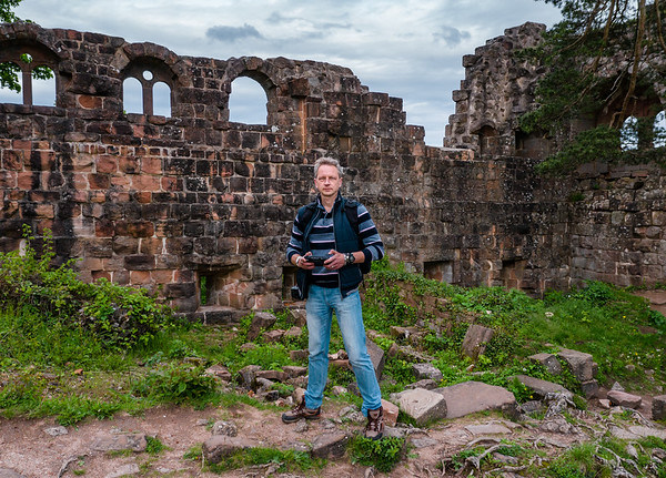 A man controls a drone and photographs himself, standing in the middle of the mountains on the ruins of a medieval castle.