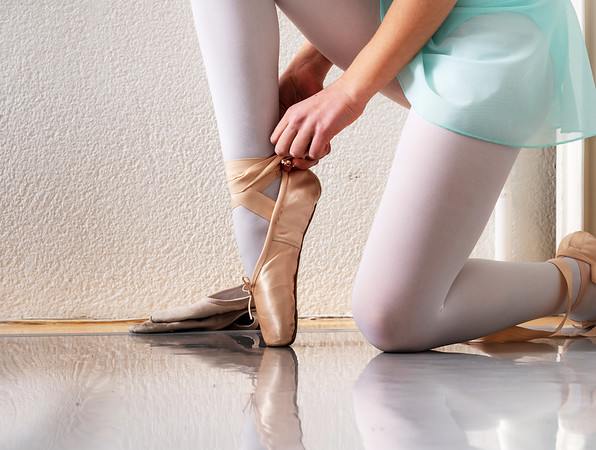 Little dancers tie pointe shoes. A lesson in classical ballet.