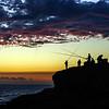 Fishermen on sunset background