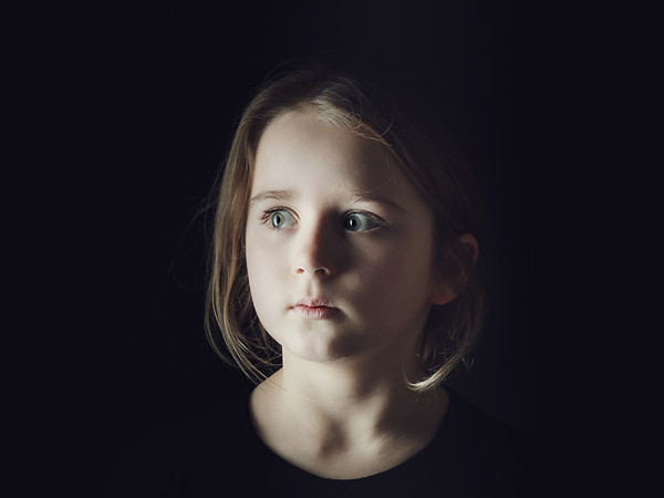 Cute little schoolgirl emotive studio portrait, isolated on black