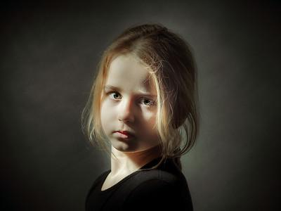 Cute little schoolgirl emotive studio portrait, isolated on black