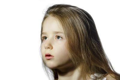 Cute little schoolgirl emotive studio portrait, isolated on white