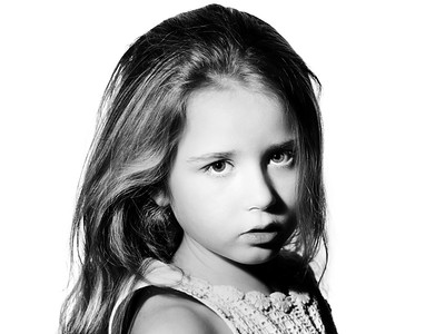 Cute little schoolgirl emotive studio portrait, isolated on white