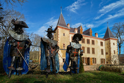 Iron statues of french musketeers on the background of an old castle