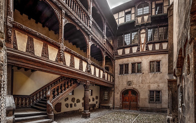 Ancient patio with wooden staircase in old timber-framing rich house XV century