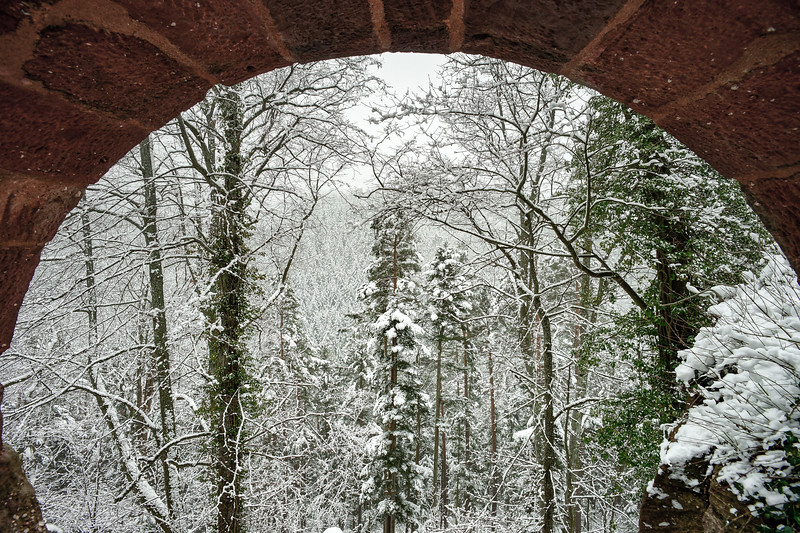 Landscape view to the winter forest through the medieval stoned arc of castle