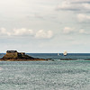 Seaside landscape with old medieval fort on the island, pirate frigate and lighthouse