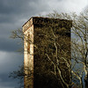 Old medieval church tower on dark stormy sky background