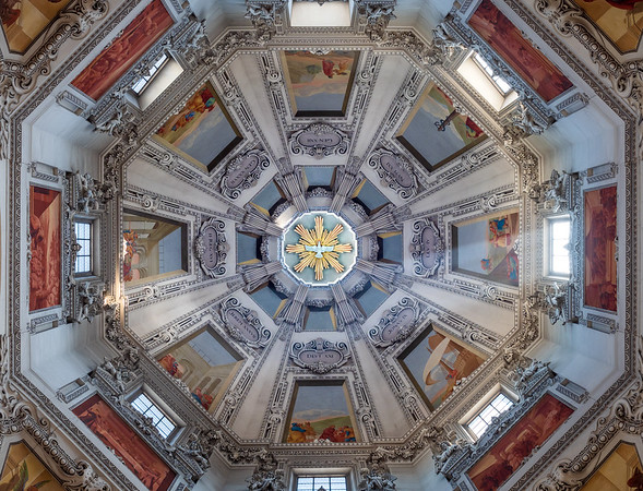 The majestic interiors of the cathedral in Salzburg. Huge dome with rich paintings