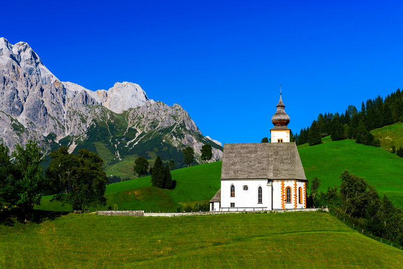 Beautiful little church in Alps. Sunny day, green grass on the hill and blue sky
