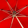 Big red sun umbrella over the street cafe