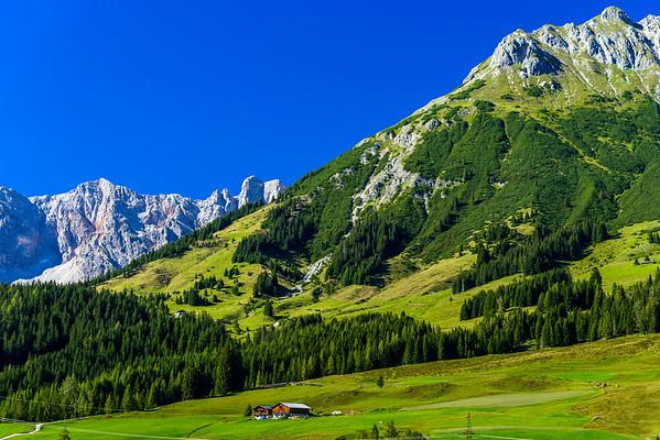 Beautiful alpine summer landscape. Mountains and sun, blue sky, calm place.