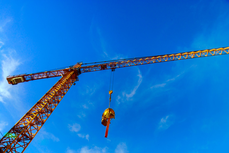 Big crane over the city on blue sky background
