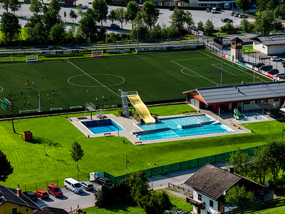 Public outdoor swimming pool in the sports complex, top view. Grossarl, Austria.