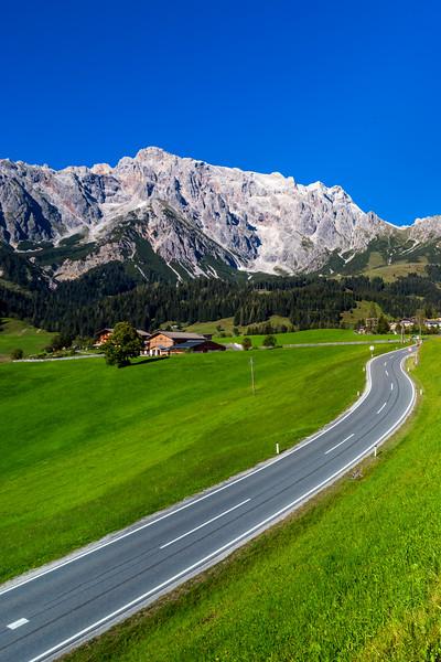 Alpine countryside road in green fields