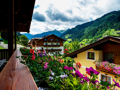 Potted flowers on balconies and terraces of wooden Austrian chalets in the small village of Grossarl. Classical tourism to Austria. Beauty, comfort and harmony. Clean air and quiet life in the Alps.