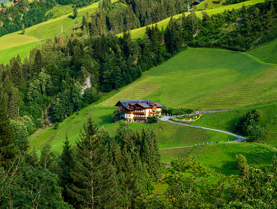 Green hills of an alpine resort in Austria in summer. Small village, hotels and chalets, all in colors. Beautiful terraces and solar panels on the roofs. The proximity of civilization and pure nature.