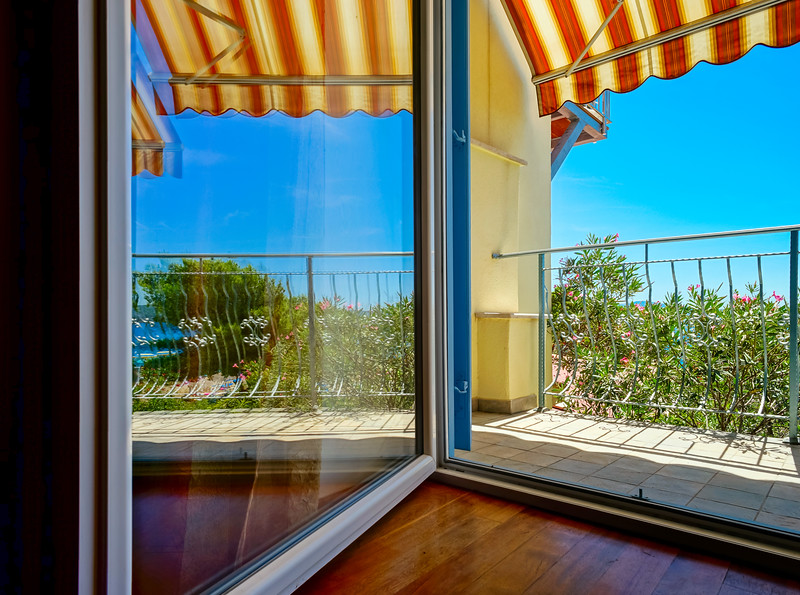 Beautiful view to sea from the inside of apartments. Balcony with marquee. Croatia.