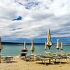 Empty sea beach with closed sun-umbrellas, Croatia, stormy weather