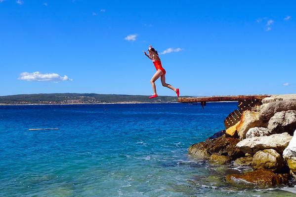 Teenage girl jumping into the sea on the sun