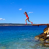 Teenage girl jumping into the sea on the sun