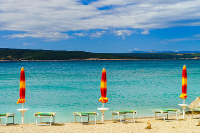 Empty sea beach with closed sun-umbrellas, Croatia, stormy weather