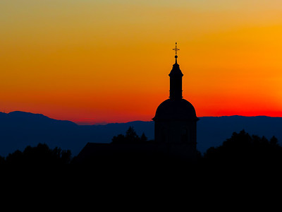 The stunning beauty and colors of the sunset overlooking the silhouettes of the Alps and the silhouette of a beautiful church