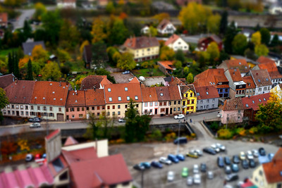 Tilt-shift miniature aerial view of red tile roofs in Schirmeck