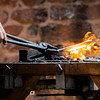 Authentic blacksmith forges metal on the anvil. Medieval traditions